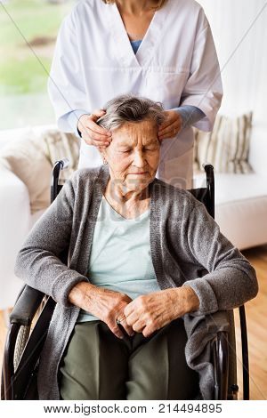 Health visitor and a senior woman during home visit. Unrecognizable nurse giving woman temple massage.