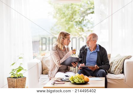 Health visitor and a senior man during home visit. A female nurse or a doctor showing test results on a tablet.