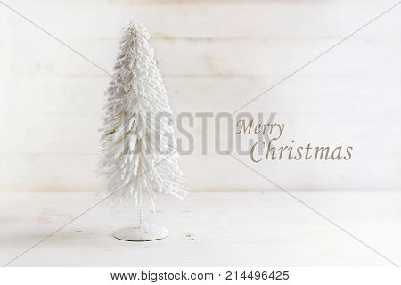 white christmas tree made of flocked wire on rustic white painted wood with text Merry Cristmas creeting card selected focus