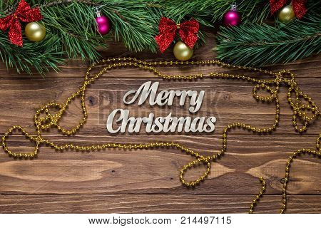 Merry Christmas title on the center of the wooden background with tinsel and a golden chaplet around poster