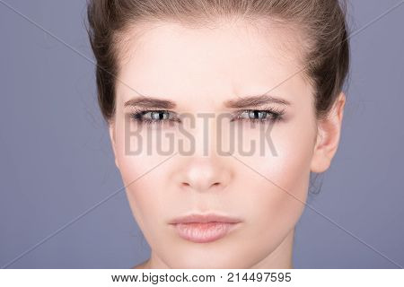Face closeup of a beautiful young woman. Perfect clean healthy skin. Emotion of discontent. His eyes were narrowed. Neutral grey background