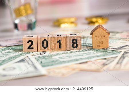 2018 new year cubes with the house model on group of cash the business finance and property concept