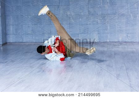 Stylish man dancing break dance. Young handsome guy in fashion casual clothes making movement with legs dancing break dance.