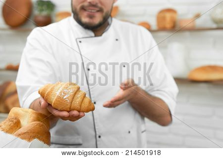 Cropped shot of a professional baker offering freshly baked delicious croissant to the viewer standing at his bakery copyspace profession occupation businessman salesperson pastry dessert.
