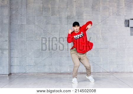 Young stylish man dancing hip-hop. Attractive hip-hop guy dancing on grey background. Street style dancing.