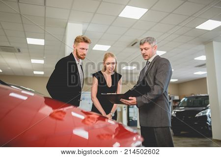Auto dealer agent showing documents with car specifications to buyers. Young family couple choosing new vehicle.