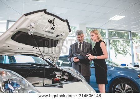 Auto dealer showing motor of electric car to young woman. Pretty female choosing car in auto showroom.
