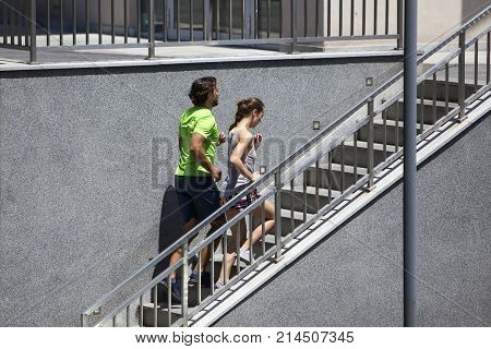 Young Couple Running Upstairs In Urban Enviroment
