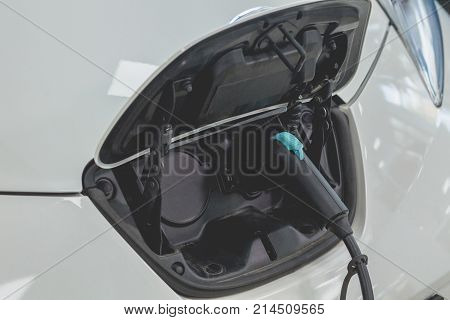 View of electric car plugged in for recharging. Electric car energy station, vehicle refilling.