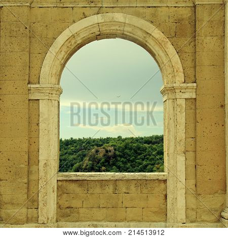 Italian view through the arch window in Sorano, Tuscany, Italy. Medieval wall with arch window in Italy