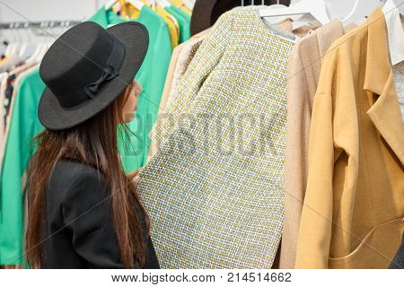 Horizontal rearview shot of a stylish woman in a hat examining clothes at the local boutique copyspace shopping consumerism fashion glamorous purchase retail sales concept.