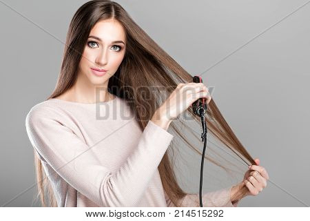 Beautiful woman ironing long  hair with hair iron. Hairstyle.