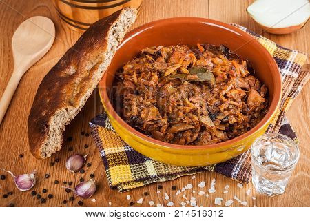 Traditional Polish bigos and fresh homemade bread closeup