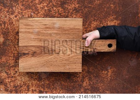Rustic Wood Cutting Board Held In Hand On Corroded Metal Textured Background