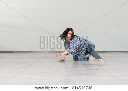 Girl in dynamic dance pose. Pretty caucasian girl dancing break dance on studio background. School of street dance.