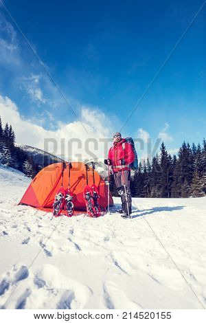 Climber Near The Tent With Snowshoes.