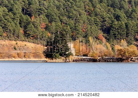 View of a mountain lake, a forest and a small church on a sunny autumn day (Greece, mountainous Corinthia)