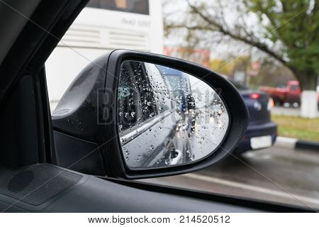 Side rear view mirror  in rainy weather. Reflection of car headlamps.