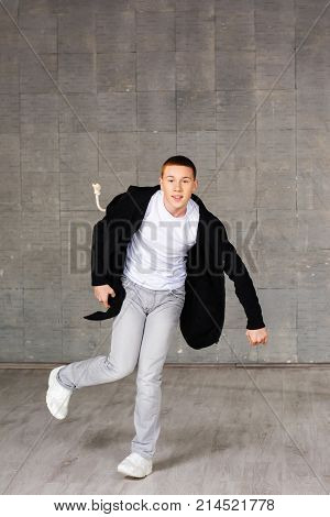 Young male contemporary style dancer. Stylish and young modern style dancer in dynamic pose on studio background. School of street dance.