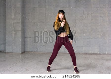 Modern style female dancer. Young woman wearing black cap and sneakers dancing hip-hop dance on grey studio background. Skillfull and talented youth.