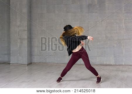 Female hip-hop dancer in motion. Young caucasian woman dancing modern dance on grey background. Street dance performance.