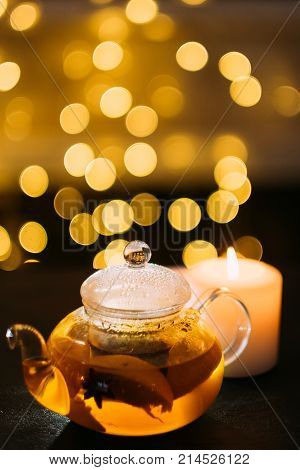 Winter hot green citrus tea with spices in a glass pot with blurred bokeh background. Flu and cold prevention and immunity reinforcement. Healthy nutrition and fitness lifestyle concept.