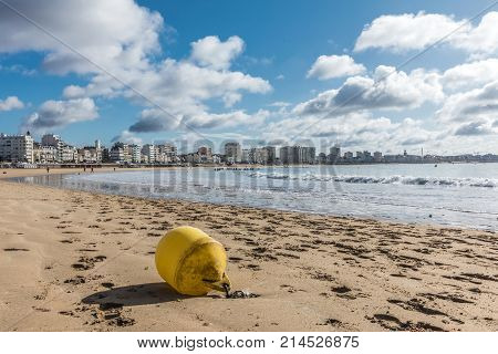 Les Sables d'Olonne beach at low tide with a yellow buoy (Vendee, France)