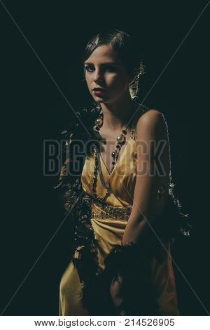 Beauty and vintage fashion. Girl in fashionable yellow dress boa fur. Woman with stylish retro hair and makeup. Pin up pretty fashion model pose on black background. Look and retro style pinup. poster