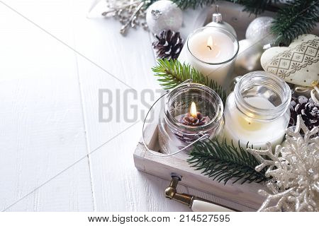 Christmas Christmas card with glowing small candle and fir cones on white wooden background, copy space