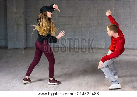 Hip-hop dancers in action. Young couple of casual dancers performing modern dance on studio background. School of dance art.