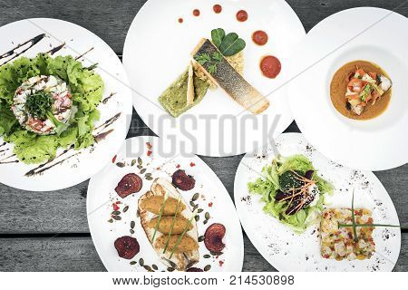 mixed modern gourmet fusion food dishes on restaurant table