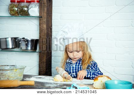 Boy Cook In Chef Hat And Apron In Kitchen
