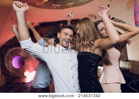A man and a woman are dancing in the foreground. Behind them they dance and sing their friends. They are all in a karaoke club and dance to modern music.