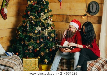 Christmas man and woman couple read book. New year guy and girl decorate Christmas tree. Couple in love in santa hat family. Winter holiday and celebration. Xmas party preparation.