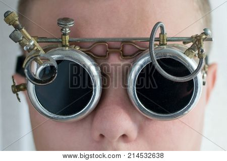 A man in metal goggles steampunk style close up