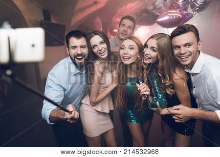Young people in the club sing songs, dance and make selfies on a smartphone with self-stick. They are smiling and posing for a photo. They are very fun and they have fun in the club.