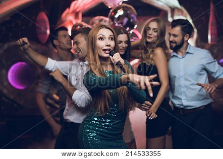A woman in a green dress is singing songs with her friends at a karaoke club. Her friends have fun on the background. Everyone is very cheerful and they smile. They are in a trendy nightclub.