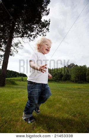 A young toddler boy running in an open grass area, excited and free