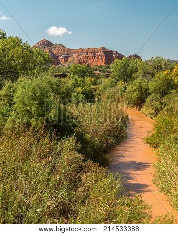 Red river running toward wall of red rock in Palo Duro Canyon near Amarillo Texas.