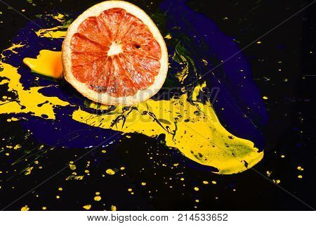 Orange or grapefruit half covered with paints. Paint splashing on grapefruit fruit. Nutrition and food art concept. Drops of blue and yellow oil or acrylic paint poured on fruit on black background.