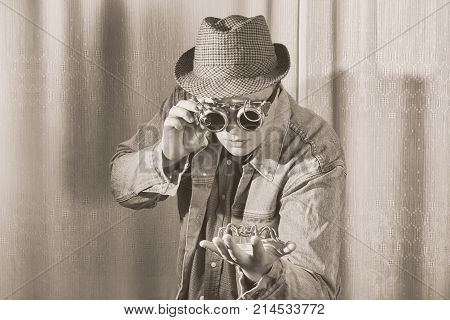 A man in goggles and hat looks at the spider sitting on his arm steampunk style black and white photo
