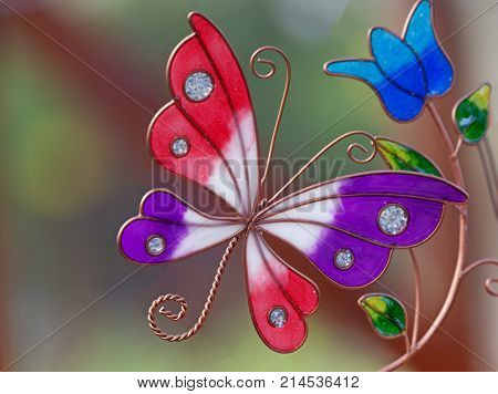 Beautiful pink purpe and white glass butterfly and blue fower with green leaves wtih a blurred background and space for text.