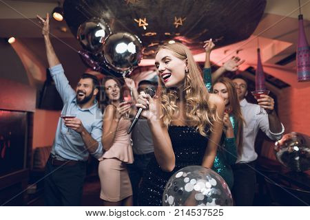 Young people have fun in a nightclub and sing in karaoke. In the foreground there is a woman in a black dress. Behind her dance her friends, with whom she came to the club.