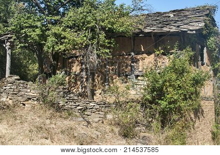 Old abandoned crumbling adobe ramshackle rickety house with stone slabs roof in late summer