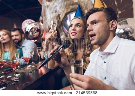 Young people are resting in a trendy nightclub. A guy in a white shirt and a girl in a black dress are singing. They have glasses with champagne in their hands and caps on their heads.