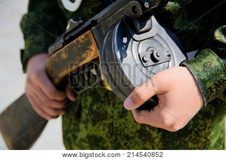 The submachine gun Shpagin in the hands of a soldier close-up with a selective focus with a shallow depth of field
