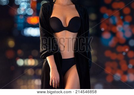 Seductive sexy woman wearing black lingerie waiting near the window at the night
