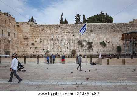JERUSALEM / ISRAEL - NOVEMBER 19 2016: People passing by and others praying to their religion at the Wailing Wall or Kotel in historic old city of Jeruslam.