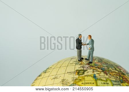 Miniature people small figure businessmen handshaking on Europe map globe as EU business agreement or Brexit negotiation concept.