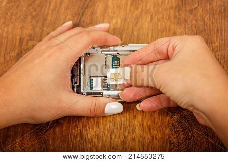 the insertion of the SIM card in a smartphone on wooden table. girl's hands insert SIM card in the phone